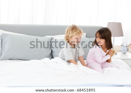 Little boy playing with his sister on their parents' bed in the morning - stock photo