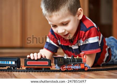 Little boy playing with railway lying on the floor - stock photo