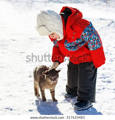 Little boy playing with the cat in the snow - stock photo