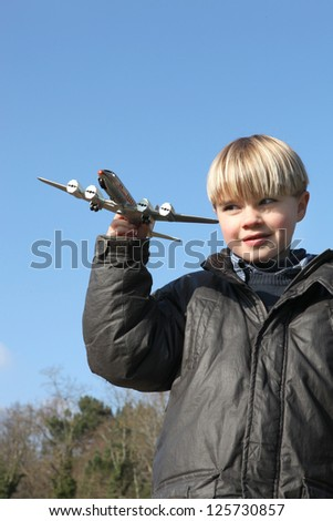 Little boy playing with toy plane - stock photo
