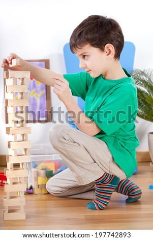 Little boy playing with toys in playroom - stock photo