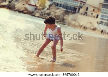 Little boy playing with water on the beach - stock photo