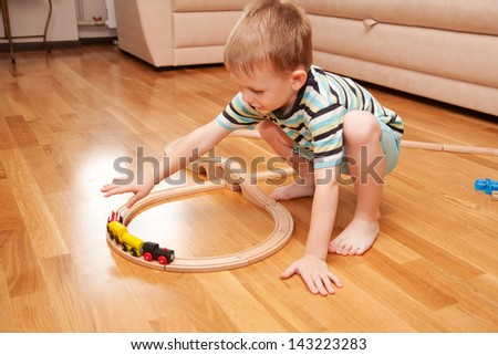 Little boy playing with wooden railway on the floor. - stock photo