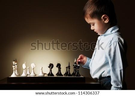 little boy plays chess - stock photo