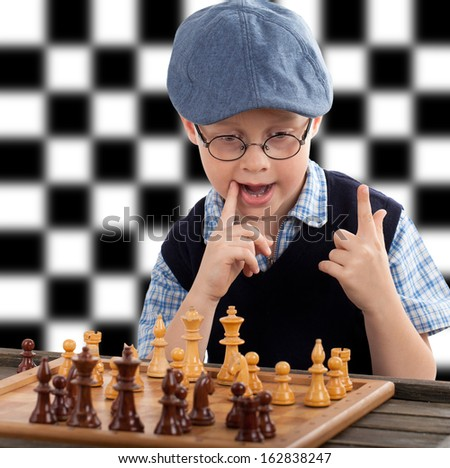 little boy plays chess, black and White chessboard in background  - stock photo