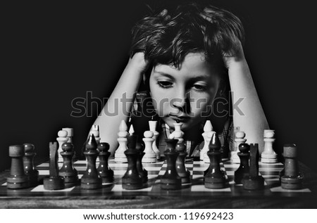 Little boy plays chess. BW - stock photo