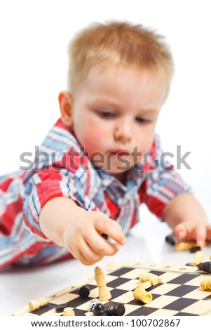 Little boy plays chess. Focus of the chess and hand. Isolated on white backround. - stock photo