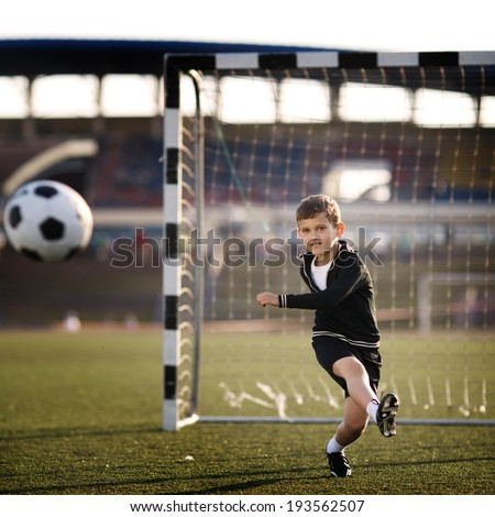 Little boy plays football on stadium - stock photo