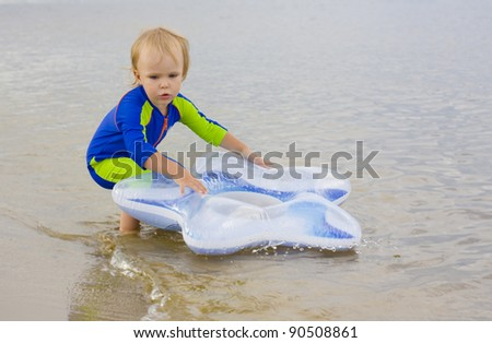 Little boy plays near the water - stock photo
