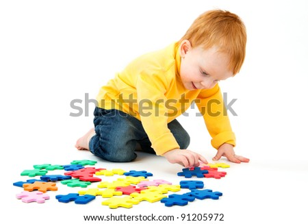 Little boy plays with a multi colored puzzle a white background - stock photo