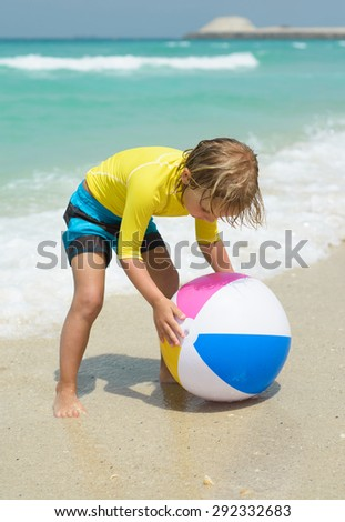 Little boy  plays with colorful beach ball - stock photo