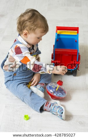 Little boy plays with colorful toy car and child's spinning top toy. Little boy plays with toys. The red-haired child playing with machine. - stock photo