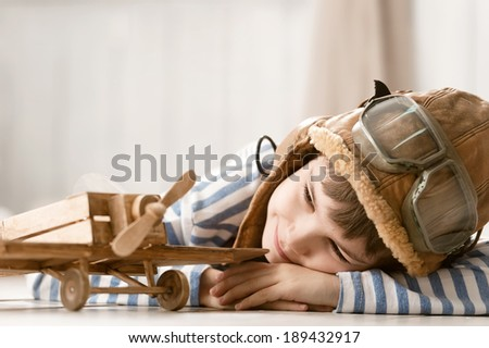 Little boy plays with wooden airplane on the floor in the room - stock photo