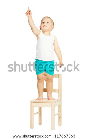 little boy points up standing on chair - stock photo