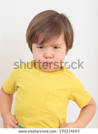 Little boy pouting. Toddler tantrum with an attitude. Grumpy preschooler wearing a yellow shirt. Two year old child on plain background, hands on hips, ready to argue and fight. Terrible twos.  - stock photo