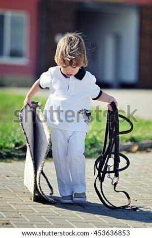 Little boy preparing to saddle up pony - stock photo