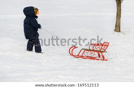 Little boy pulling a sled through winter snow in his thick winter clothes as he trudges backwards up the slope for another run - stock photo