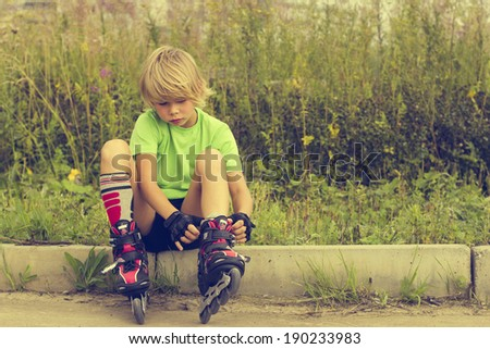 Little boy puts rollers sitting on the roadside. - stock photo