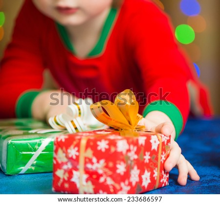 little boy reaching for christmas gift box - stock photo