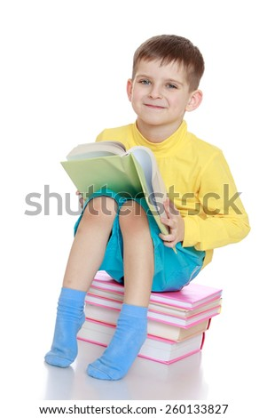 little boy reading a book sitting on a chair from textbooks - isolated on white. - stock photo