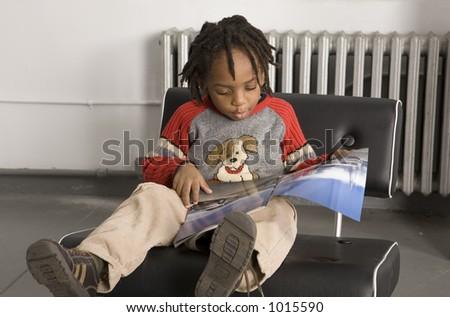 Little boy reading a magazine - stock photo