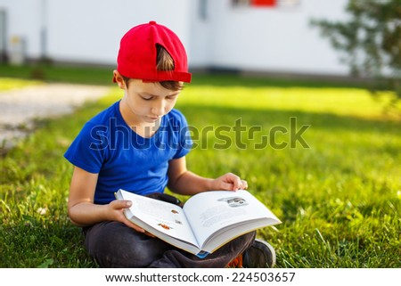 Little boy reading fable book, outdoor portrait - stock photo