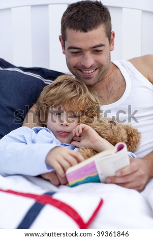 Little boy reading with his father a book in bed - stock photo