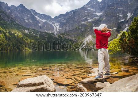 Little boy relax on mountain lake coast - stock photo