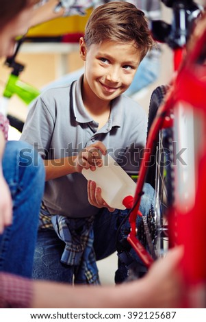 Little boy repairing his bicycle - stock photo