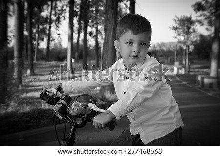 Little boy rides his bicycle in summer afternoon in the park. Nice baby dressed casual. Outdoor black & white  picture. - stock photo