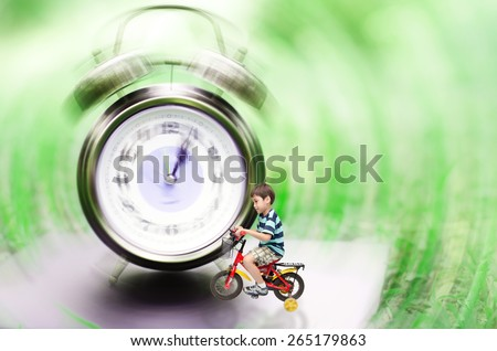 Little boy riding bicycle pass the clock time machine back to the past or future - stock photo