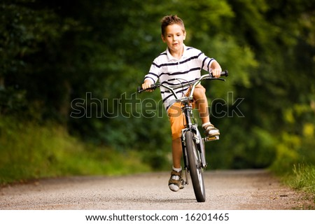 Little Boy riding his bicycle on a dirt road in the woods - stock photo