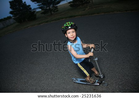 Little boy riding scooter outdoors - stock photo