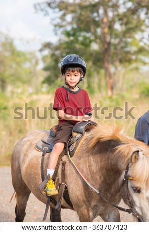 Little boy riding training horse - stock photo