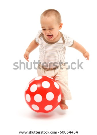 Little boy running and playing with spotty red ball - stock photo