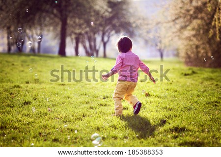 Little boy, running in the park, chasing soap bubbles, nice afternoon back light - stock photo