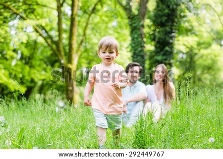 Little boy running over meadow with family in back - stock photo