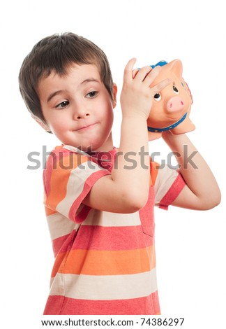 Little boy shaking the piggy bank to find out the contents isolated on white - stock photo