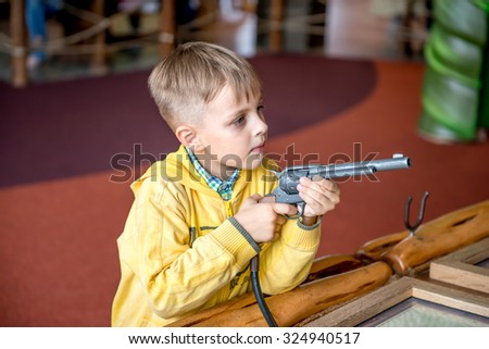 Little boy shooting with revolver gun in amusement park - stock photo