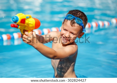 Little boy shooting with water gun in the pool - stock photo