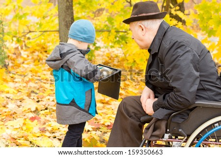 Little boy showing his handicapped grandfather who is confined to a wheelchair by a leg amputation something on his tablet computer as the two enjoy a day out in a colourful autumn park - stock photo