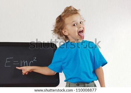 Little boy shows tongue like Einstein near formula on a blackboard - stock photo