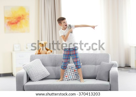 Little boy singing with a microphone on a sofa at home - stock photo