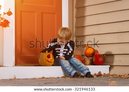 Little Boy Sits Near Halloween Pumpkin In The Courtyard. Halloween Theme - stock photo