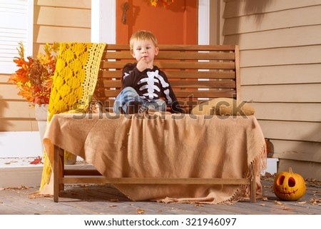 Little Boy Sits On Bench Near Halloween Pumpkin In The Courtyard. Halloween Theme - stock photo