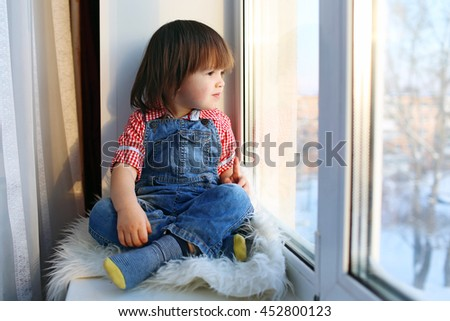 little boy sits on sill and looks out of window in wintertime - stock photo