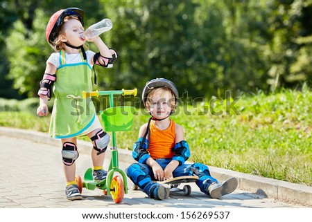 Little boy sits on skateboard next to little girl, who drinks water from plastic bottle, standing with three-wheeled scooter - stock photo