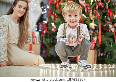 Little boy sits squatted among burning tealights that stand on floor in shape of heart under Christmas tree, teenage girl sits on floor a little further not in focus - stock photo
