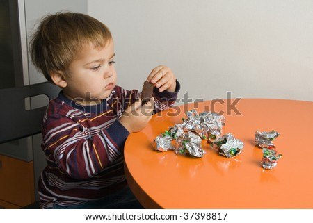 Little boy sitting at a table eating chocolates - stock photo