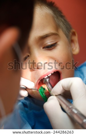 Little boy sitting at dentist, his teeth being drilled - stock photo